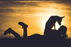Schattenbild des Mädchens mit dem Hund, der durch Sonnenuntergang sich entspannt Lizenzfreies Stockbild
