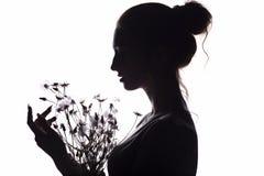 Schattenbild des Mädchens mit einem Blumenstrauß mit des Löwenzahns, Gesicht der jungen Frau auf einem Weiß lokalisierte Hintergr lizenzfreie stockbilder