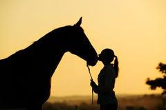 Schattenbild des Mädchens mit Pferd bei dem Sonnenuntergang Lizenzfreies Stockfoto