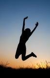 Schattenbild des Mädchens springend auf dem Gebiet stockfotografie