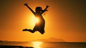 Schattenbild des Mädchens springend bei Sonnenaufgang auf dem Strand stock video footage