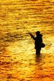 Schattenbild des Mann-Flyfishing Fischens im Fluss-goldenen Sonnenlicht, das ihn Fischer des frühen Morgens umgibt lizenzfreie stockbilder