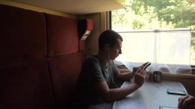 Schattenbild des Mannes auf einem Zugbahnauto hörend Musik auf Kopfhörern eine Mitteilung in Social Media eines Boten schreibend stock video footage