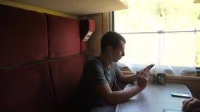 Schattenbild des Mannes auf einem Zugbahnauto hörend Musik auf Kopfhörern eine Mitteilung in Social Media eines Boten schreibend stock footage
