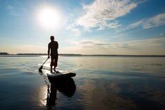 Schattenbild des Mannes, der auf einem SUP-Brett ausbildet Lizenzfreie Stockfotos