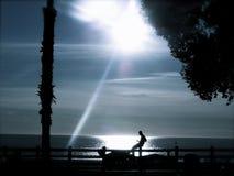 Schattenbild des Mannes durch das Meer an der Dämmerung Stockbild