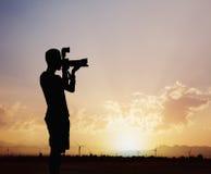 Schattenbild des Mannes Fotos mit seiner Kamera bei Sonnenuntergang mit einem drastischen Himmel machend Lizenzfreies Stockbild