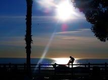 Schattenbild des Mannes Gitarre durch das Meer an der Dämmerung spielend Lizenzfreie Stockfotografie