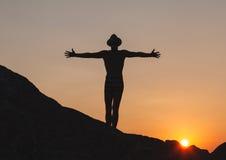 Schattenbild des Mannes Hände auf der Klippe anhebend Stockfotografie