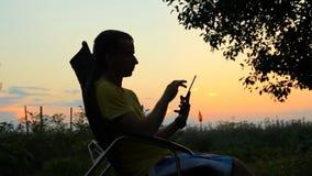Schattenbild des Mannes im Stuhl, der in der Tablette spielt Vor dem hintergrund eines orange Himmels nach Sonnenuntergang stock video footage
