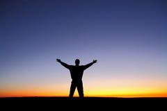 Schattenbild des Mannes mit den Armen streckte am Sonnenuntergang aus Stockbild