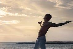 Schattenbild des Mannes mit den ausgestreckten Armen auf Himmelhintergrund stockfotografie