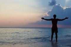 Schattenbild des Mannes mit den ausgestreckten Armen auf Strand Stockbild