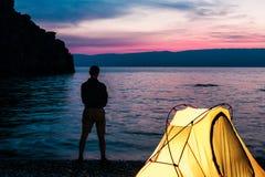 Schattenbild des Mannes nahe Zelt am See Stockfotos