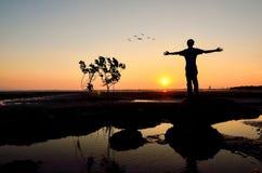 Schattenbild des Mannes seine Hände oder offenen Arme anhebend Stockbild
