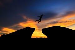 Schattenbild des Mannes springend über Klippe auf Sonnenunterganghintergrund, Lizenzfreies Stockfoto