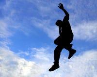 Schattenbild des Mannes springend in einer Luft Lizenzfreies Stockfoto