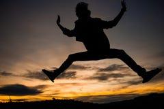 Schattenbild des Mannes springend mit Sonnenunterganghimmel für Hintergrund Stockbild