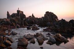 Schattenbild des Mannes stehend auf dem Felsen Stockfotografie