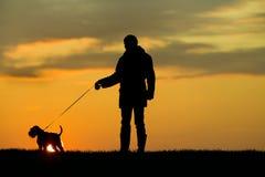 Schattenbild des Mannes und des Hundes Stockfotos