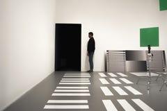 Schattenbild des Mannes unter geometrischen Gegenständen im Kunstausstellungsraum Lizenzfreie Stockfotos