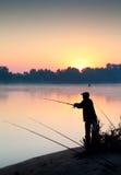 Schattenbild des Mannfischens in einem Sonnenuntergang lizenzfreie stockbilder