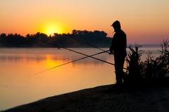 Schattenbild des Mannfischens in einem Sonnenuntergang Lizenzfreies Stockfoto