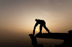 Schattenbild des Mannhandreichungsfreunds auf Berg Stockfoto