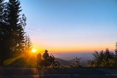 Schattenbild des Mannradfahrers und des Abenteuermotorrades auf der Straße mit Sonnenunterganglichthintergrund Spitze von Bergen, lizenzfreie stockbilder
