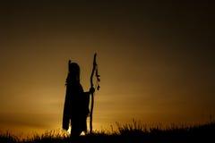 Schattenbild des Medizinmanns des amerikanischen Ureinwohners mit Pikenschaft auf backgroun Lizenzfreie Stockfotografie