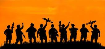 Schattenbild des Militärsoldaten oder des Offiziers mit Waffen bei Sonnenuntergang Lizenzfreies Stockfoto
