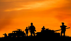 Schattenbild des Militärsoldaten oder des Offiziers mit Waffen bei Sonnenuntergang Lizenzfreies Stockbild