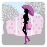 Schattenbild des modernen Mädchens gehend hinunter die Straße mit einem Regenschirm in seiner Hand Lizenzfreie Stockfotos