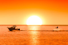 Schattenbild des Motorboots und des Wakeboarders bei dem Sonnenuntergang, der Trick durchführt Stockbilder