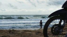 Schattenbild des Motorrads und der Frau am Strand Stockbilder