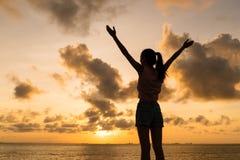 Schattenbild des offenen Armes der Frau unter Skylinen am Abend Lizenzfreies Stockbild