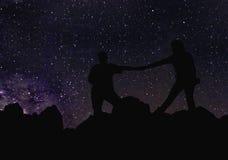 Schattenbild des Paarhändchenhaltens unter den Sternen, Milchstraße und viele Sterne über dem Berg bei Wadi Rum verlassen Lizenzfreie Stockfotos