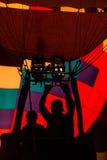 Schattenbild des Piloten im Heißluftballonkorb unter Verwendung des Brenners mit schönem farbigem Umschlag im Hintergrund lizenzfreie stockfotos