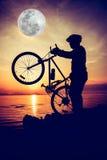 Schattenbild des Radfahrers die Ansicht an der Küste genießend draußen Stockfotos