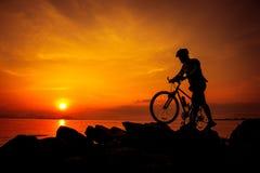 Schattenbild des Radfahrers die Ansicht an der Küste genießend draußen Stockfotografie