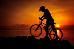 Schattenbild des Radfahrers die Ansicht an der Küste genießend draußen Lizenzfreie Stockfotos