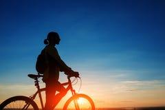 Schattenbild des Radfahrers und des Fahrrades auf Himmelhintergrund Stockfoto