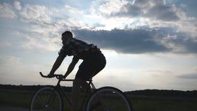 Schattenbild des Reitens des jungen Mannes am Weinlesefahrrad mit schönem Sonnenunterganghimmel am Hintergrund Kerl, der in das L stock footage