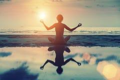 Schattenbild des schönen Mädchens sitzend auf dem Strand und in der Yogahaltung meditierend lizenzfreie stockfotos