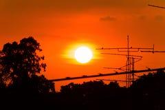 Schattenbild des schönen Sonnenuntergangs mit Fernsehantenne oder Telekommunikation ragt, orange Himmel mit Wolken hoch stockfoto