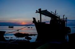 Schattenbild des Schiffs mit Sonnenunterganghimmel in Meer Lizenzfreies Stockfoto