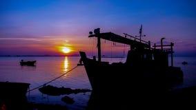 Schattenbild des Schiffs mit Sonnenunterganghimmel in Meer Stockfotografie