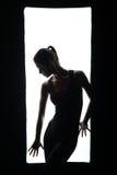 Schattenbild des schlanken Mädchens aufwerfend im Rahmen Stockfotografie