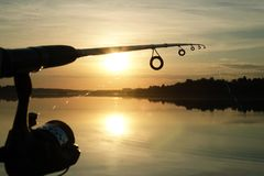 Schattenbild des Spinnens Fischerei bei Sonnenuntergang liebhaberei lizenzfreie stockbilder