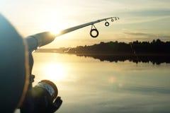 Schattenbild des Spinnens Fischerei bei Sonnenuntergang liebhaberei lizenzfreie stockfotos